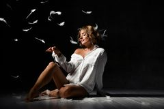 Free Beautiful Young Blonde Is Sitting On The Floor In One White Shirt Having Fun With Feathers. Stormy Night. Royalty Free Stock Photography - 163126507