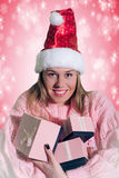 Beautiful young blonde lady with charming smile. A portrait of smiling blonde lady wearing red Santa Claus hat embracing Christmas gifts on tender pink Stock Image