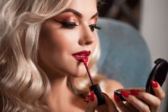 Beautiful young blonde makes a bright holiday makeup. Glamorous make-up. stock photos