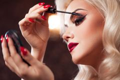 Beautiful young blonde makes a bright holiday makeup. Glamorous make-up. royalty free stock photos