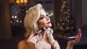 Beautiful young blonde makes a bright holiday makeup. Glamorous make-up. An attractive young woman uses powder. stock photography