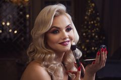 Beautiful young blonde makes a bright holiday makeup. Glamorous make-up. An attractive young woman uses powder. royalty free stock photography
