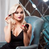 Beautiful young blonde makes a bright holiday makeup. Glamorous make-up. royalty free stock photo