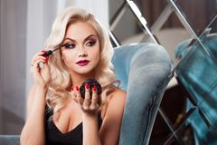 Beautiful young blonde makes a bright holiday makeup. Glamorous make-up. stock images