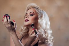 Beautiful young blonde makes a bright holiday makeup. Glamorous make-up. royalty free stock photography