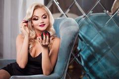 Beautiful young blonde makes a bright holiday makeup. Glamorous make-up. stock photos