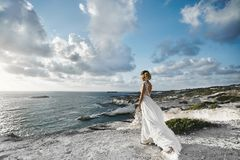 Free Beautiful Young Blonde Model Girl, In White Dress, Stands Half Sideways At The Coast And Looks At The Sea Stock Photo - 110213600