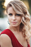 Beautiful young blonde model in a red dress posing Royalty Free Stock Photos