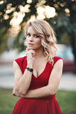 Beautiful young blonde model in a red dress posing Stock Images