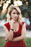 Beautiful young blonde model in a red dress posing Stock Photos