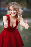 Beautiful young blonde model in a red dress posing Royalty Free Stock Photography