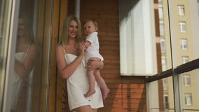 Beautiful young blonde mom playing with her baby boy son - Family values goal - Caucasian mother and child at home -. Smooth cinematic handheld movement stock video footage