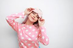 Beautiful young blonde in pink pajamas and a sleep mask. Girl woke up in the morning, concept of cheerful beginning of day royalty free stock images
