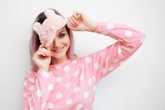 Beautiful young blonde in pink pajamas and a sleep mask on eyes. Girl woke up in the morning, concept of cheerful beginning of day stock images
