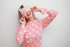 Beautiful young blonde in pink pajamas and a sleep mask on eyes. Girl woke up in the morning, concept of cheerful beginning of day stock photos