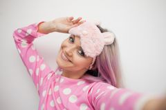 Beautiful young blonde in pink pajamas and a sleep mask. Selfie portrait, cheerful morning. Concept stock image