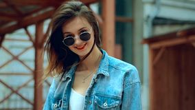 Beautiful young blonde with red lips in sunglasses walks and smiles on camera