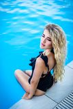Beautiful young blonde is sitting on the edge of the pool. Sensual sexy woman on the background of the pool. Relax by the pool. Stock Images