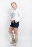 Beautiful young blonde in a white blouse, blue shorts and high boots posing Stock Image