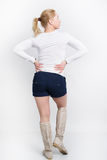 Beautiful young blonde in a white blouse, blue shorts and high boots posing Stock Photography