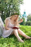 Beautiful young blonde woman. Beautiful young blonde woman reading a book on the green background of the summer Royalty Free Stock Photography