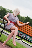 Beautiful young blonde woman on bench Stock Photography