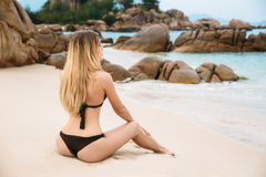 Beautiful young blonde woman in black bikini posing on the beach in turning booty shows ass. Sexy model portrait with Stock Images