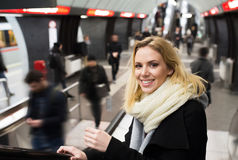 Young woman standing at the escalator in Vienna subway. Beautiful young blonde woman in black coat and big woolen scarf standing at the escalator in Vienna Royalty Free Stock Image