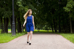 Beautiful young blonde woman in blue dress Stock Images