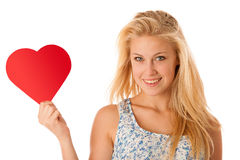 Beautiful young blonde woman with blue eyes holding red hart ban. Ner for valentines day isolated over white Stock Image