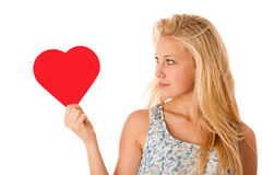 Beautiful young blonde woman with blue eyes holding red hart ban. Ner for valentines day isolated over white Stock Photography