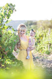 Beautiful young blonde woman with a child girl in the field of g. Beautiful young mother spends time with her infant daughter outside in the fields of grapes Stock Image