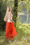 Beautiful young blonde woman dancing in forest on riverbank Royalty Free Stock Image