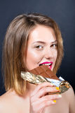 Beautiful young blonde woman eating chocolate bar. Stock Photos