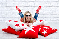 Beautiful young blonde woman in glasses lying on the pillow. Beautiful pillows to decorate the interior of the house. Pillow with. Beautiful pillows to decorate royalty free stock photography