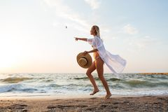 Beautiful young blonde woman with hat walking at the beach. Picture of beautiful young blonde woman with hat running outdoors at the beach pointing Royalty Free Stock Image