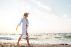Beautiful young blonde woman with hat walking at the beach. Picture of beautiful young blonde woman with hat walking outdoors at the beach Stock Images