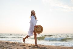 Beautiful young blonde woman with hat walking at the beach. Picture of beautiful young blonde woman with hat walking outdoors at the beach Royalty Free Stock Photos