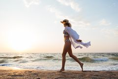 Beautiful young blonde woman with hat walking at the beach. Picture of beautiful young blonde woman with hat walking outdoors at the beach Royalty Free Stock Photography