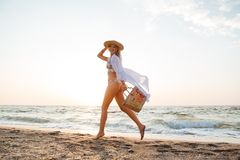 Beautiful young blonde woman with hat walking at the beach. Picture of beautiful young blonde woman with hat walking outdoors at the beach Stock Photos