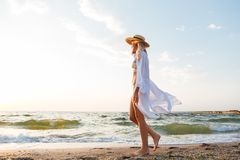 Beautiful young blonde woman with hat walking at the beach. Picture of beautiful young blonde woman with hat walking outdoors at the beach Stock Image