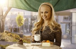 Beautiful young woman having cake outdoors Royalty Free Stock Images