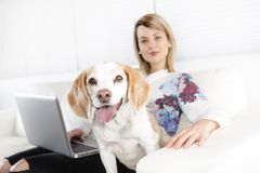 Beautiful young blonde woman with her dog at home. A Beautiful young blonde woman with her dog at home Royalty Free Stock Photography