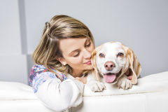 Beautiful young blonde woman with her dog at home Royalty Free Stock Image