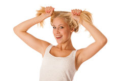 Beautiful young blonde woman holds hair in her hand gesturing ex Stock Image