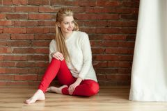 Free Beautiful Young Blonde Woman In A White Warm Jacket And Red Zhdinsah, Sits On The Floor Near The Window, Against A Red Brick Wall Stock Photos - 105886493