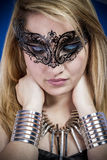 Beautiful young blonde woman with jewelry and silver bracelets,. Venetian mask, rockstar Royalty Free Stock Image