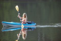 Beautiful young blonde woman kayaking on lake Royalty Free Stock Photography