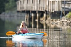 Beautiful young blonde woman kayaking on lake Stock Photography