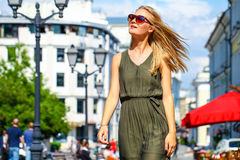 Beautiful young blonde woman in long dress. Close up, attractive young blonde woman in long dress walking in summer street Royalty Free Stock Image